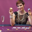 Woman at poker game holding up chips - ストック写真