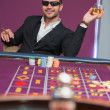 Man in sunglasses at roulette table - ストック写真