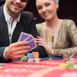 Couple sitting at the poker table smiling  — Stock Photo