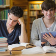Young man with tablet pc in the library — Stock Photo #23088692