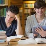 jonge man met tablet pc in de bibliotheek — Stockfoto #23088692