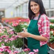 Worker holding a flower and smiling — Stock Photo