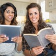 Smiling girls reading a book and holding a tablet computer — Stock Photo