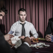 Serious man looking up from high stakes poker game — Stock Photo #23088750