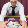 Happy man at poker table taking his winnings - Stock Photo