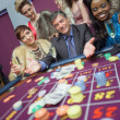 Man surrounded by women at roulette table — Stock Photo