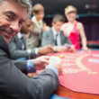 Man smiling at the poker table — Stock Photo