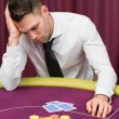 Mleaning on poker table looking disappointed — Foto de stock #23088920