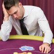 Mleaning on poker table looking disappointed — Stock fotografie #23088920