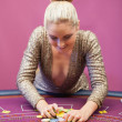 Woman in a casino grabbing chips — Stock Photo