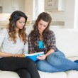 Women sitting on a couch while looking at a notepad — Stock Photo