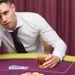 Mleaning on poker table drinking whiskey — Stock Photo #23089070