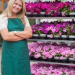 Florist having arms crossed standing in garden center - Stock Photo