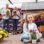 Happy family holding flower pots — Stock Photo #23089262