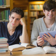 Young men looking up from studying in library — Stock Photo #23089308