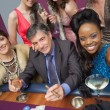 Man surrounded by beautiful women at roulette table — Stock Photo
