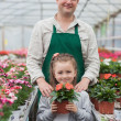 Gardener and little child holding a flower — Stock Photo