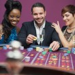 Man playing roulette with two women — Stock Photo #23089608