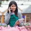 Employee talking on phone while checking flowers - Stock Photo