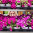 Stock Photo: Woman looking through shelves in flowers store