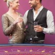 Couple drinking champagne at poker table — Stock Photo #23089746