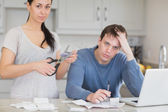 Disappointed couple in the kitchen cutting credit card — Stock Photo
