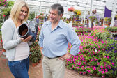 Couple smiling and looking at boot shaped flower pot — Stock Photo