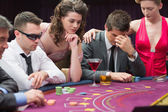 Man losing at poker table with woman comforting him — Stock Photo