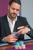Man holding a cigar looking at his cards — Stock Photo