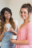 Smiling women holding coffee cups — Stock Photo