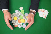Hands grabbing dollars and chips from table beside royal flush — Stock Photo