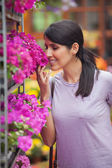 Woman smelling flowers in garden center — Stok fotoğraf