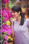 žena vonící květy v zahradním centru — Stock fotografie