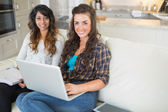 Happy girls using laptop for homework — Stock Photo