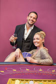 Happy couple at poker table — Stock Photo