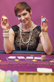 Woman holding chips in her hand in a casino — Stock Photo