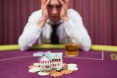 Człowiek jest licytacji domu w pokera — Zdjęcie stockowe