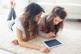 Two women looking at tablet pc on floor — Stock Photo