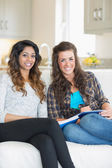 Two smiling girls sitting on a couch while writing on a notepad — Stock Photo
