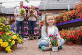 Family holding flower pots in garden center — Stock Photo