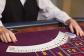 Dealer dealing out cards at roulette table — Stock Photo