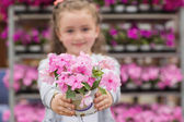 Little girl with flowers in garden center — Stock Photo