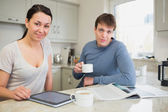 Smiling woman with tablet pc and man with newspaper — Stock Photo