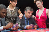 Man playing poker with two women beside him — Photo