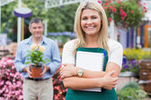 Woman holding a notepad with customer holding potted plant — Stock Photo
