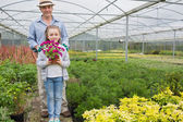 Gardener standing with granddaughter holding a flower pot — Foto Stock