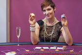 Woman at poker game holding up chips — Stock Photo