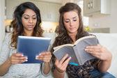 Meninas, lendo um livro e segurando um computador tablet — Fotografia Stock