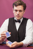 Dealer sitting in a casino while shuffling cards — Stock Photo