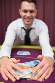 Man grabbing money at poker table — Stock Photo